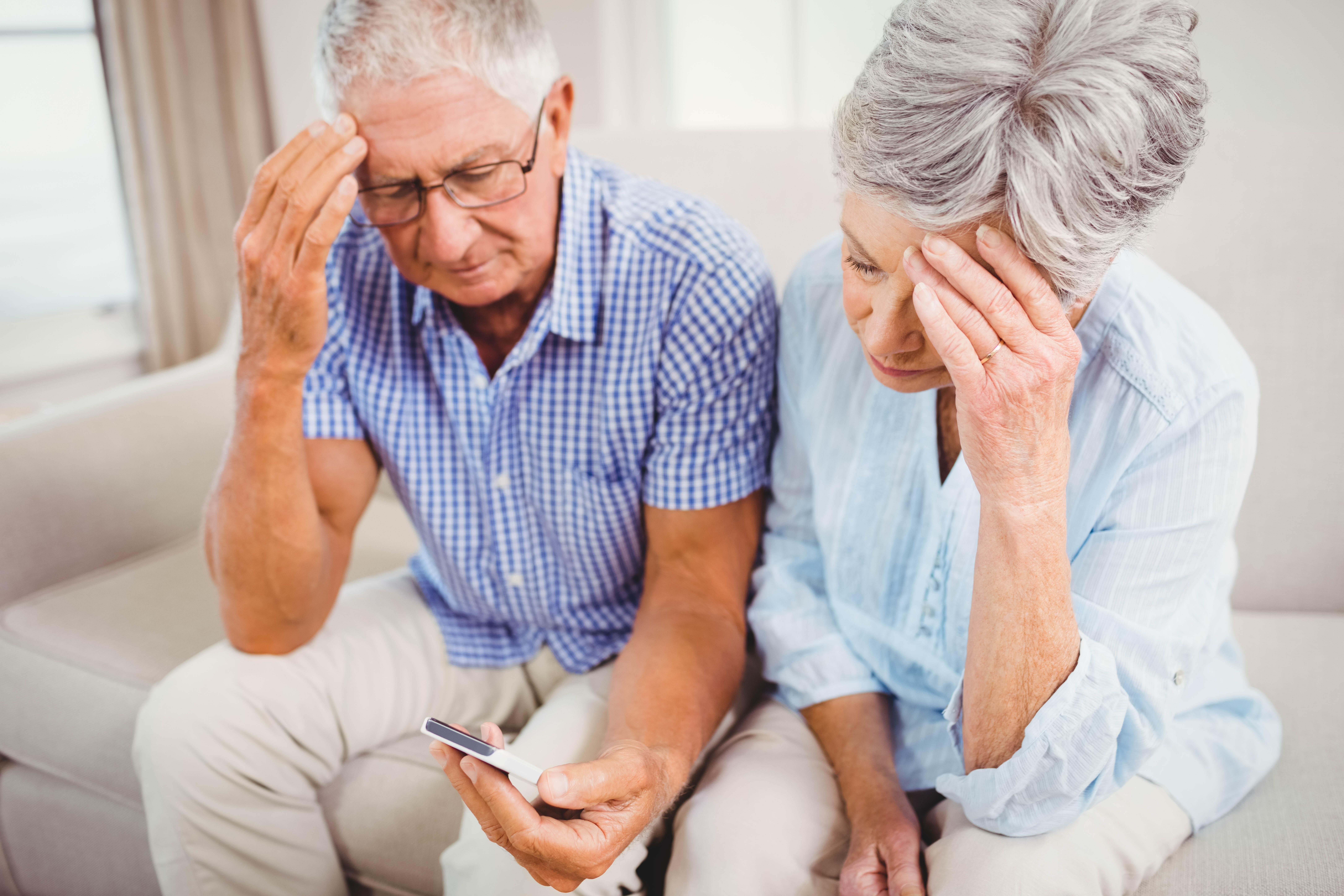 Sad senior couple looking at mobile phone
